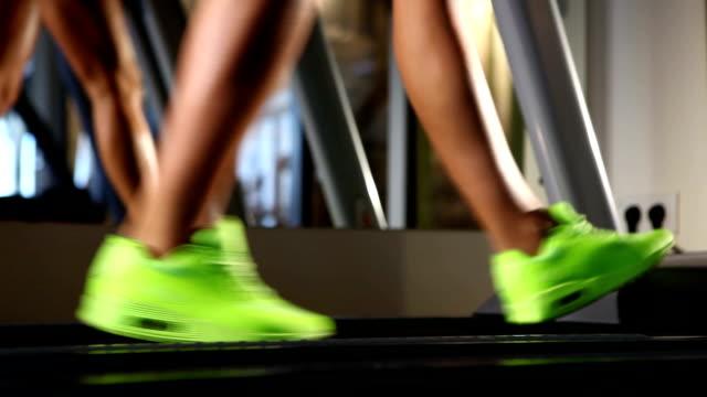 woman's muscular legs on treadmill, closeup video