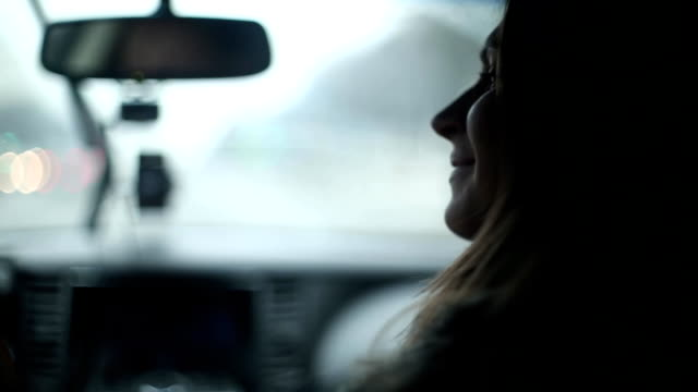 Womans silhouette kissing her lover on a cheek and smiling in a car. Man is driving a car. Traveling by car video