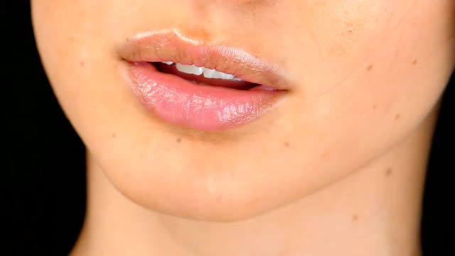 Woman's tongue seductively licking lips, close up,slow motion video
