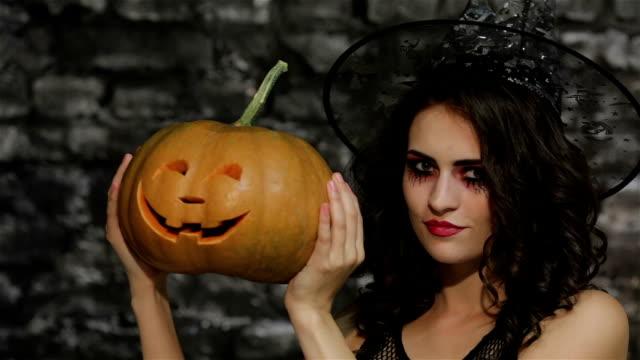 A woman-sorceress covers her face pumpkin video