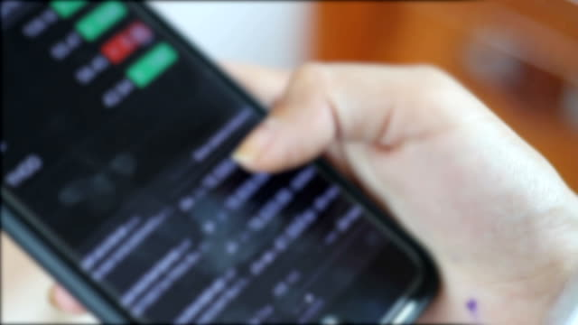 women asian using smartphone for looking and analyzing stock trend market data video