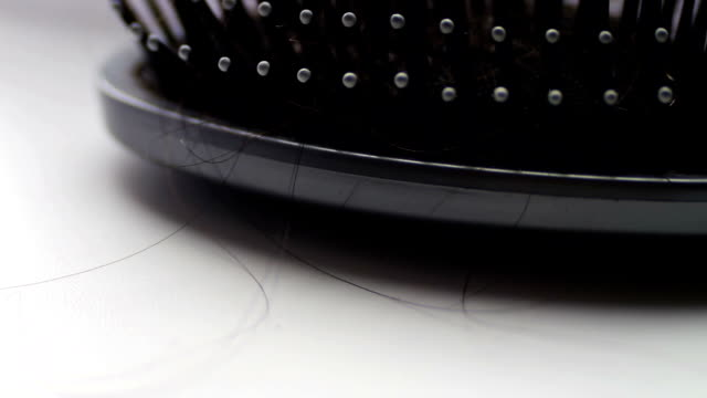 Women comb hair,hairbrush with hair extreme macro close up view, near black hair clips video