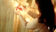 Women decorates the house. light garland and flags video