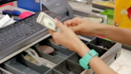 Women dispensing change and counting from a register cash drawer video