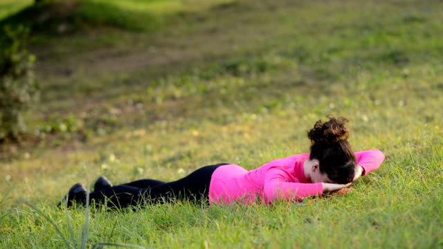women doing fitness exercise for the back outdoors in the park video