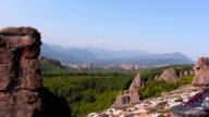 Women feet in sport shoes step on a rock, tourist admire the Belogradchik valley video