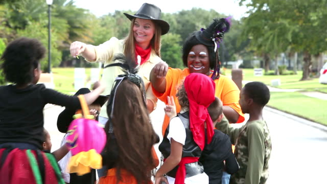 Women giving out candy to children in halloween costumes video