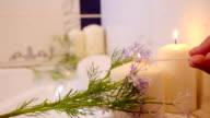Women hand burns candles in bathroom. Spa still life. video