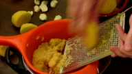 Women hands with a grater grate the potatoes on the for potato pancakes video