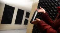 A women holds a bottle of wine in an aging cellar.Bordeaux Wineyard video
