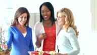 Women in kitchen talking about food on counter video