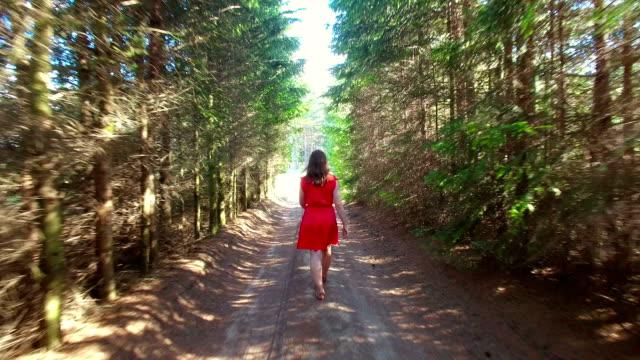 Women in red dress walking in the tree alley video