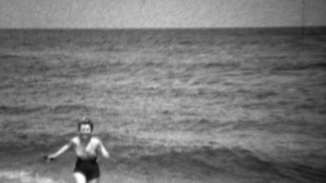 1936: Women in swimsuit scared of swimming in ocean waves. video