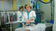 Women ironing clothes at a laundry shop video