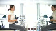 Women is exercising with dumbbells in gym video