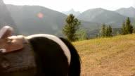 Women leads horses across mountain meadow video