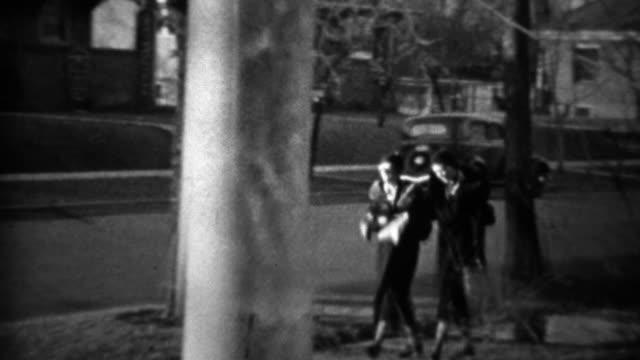 1933: Women on neighborhood sidewalk past classic model A car. video