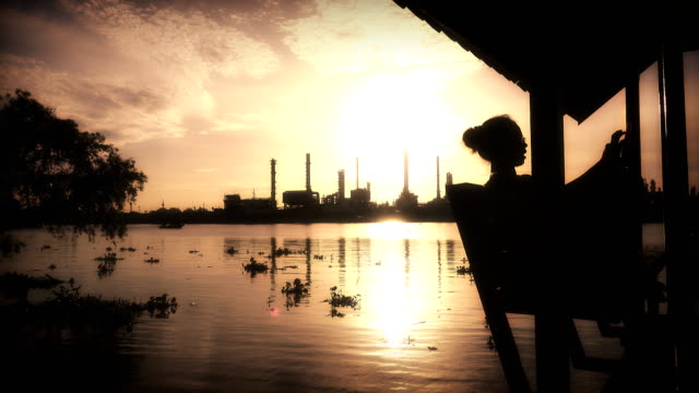 Women playing phone at Oil refinery plant at twilight morning. video