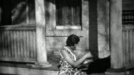 1934: Women plays with black dog on front stoop house porch. video