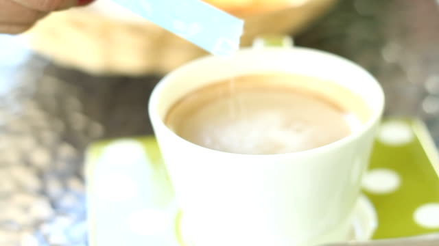 women pouring sugar into a cup of coffee video