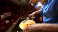 Women preparing food in cabin of sailboat video