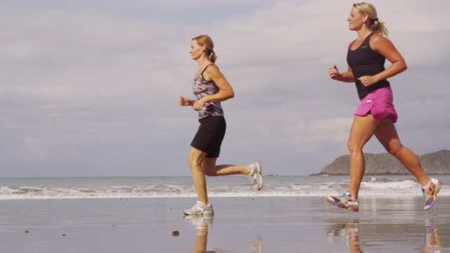 Women running on beach, slow motion. video