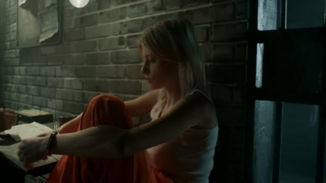 Women sitting by guard in prison video