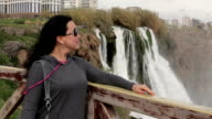 Women standing on the bridge in the park on the background  Duden Waterfall in Antalya, Turkey video