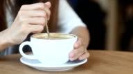 Women stir latte art coffee white up in cafe, Closeup video