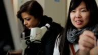 Women students Indian and Asian attend a practical training with optical microscopes video