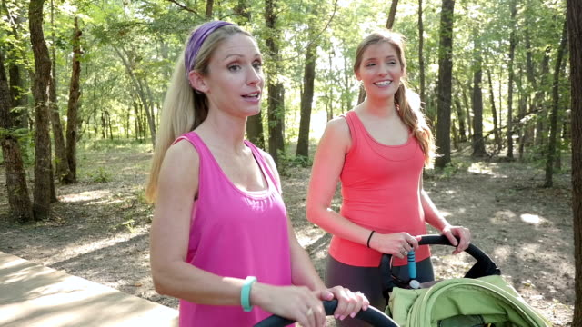 Women talking after run in park with jogging strollers video
