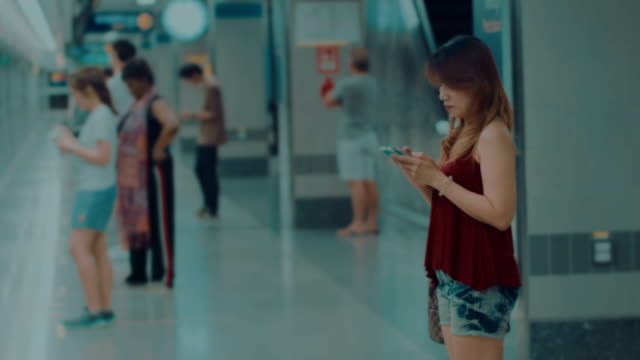 women using cellphone at subway station video