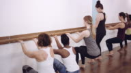 Women using wall railing to exercise video