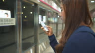 Women waiting The train and Using smart phone video