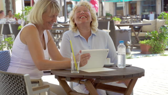 Women watching something funny on tablet PC in outdoor cafe video