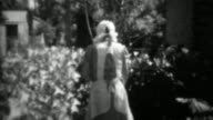 1933: Women watering garden with finger over hose end. video