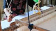 Women weaving cotton on a loom in Thailand video