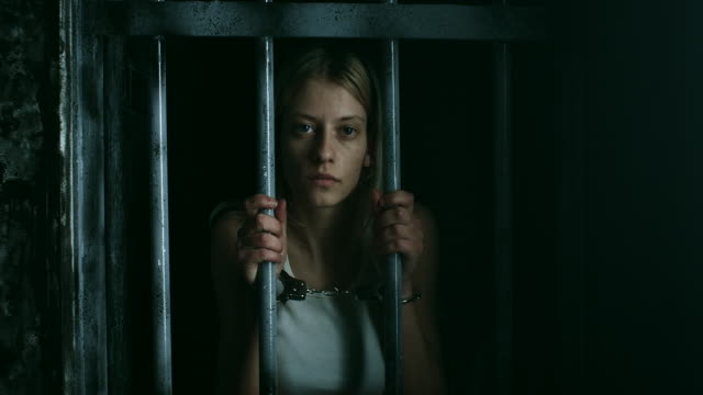 Women with handcuffs holding bars and looking through video