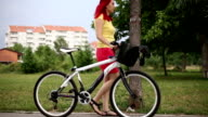 Women with red hair walking with bicycle video