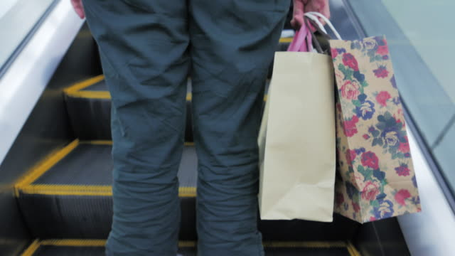 Women with shopping bags on escalator video