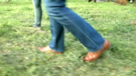 Women's feet on the grass in shoes and sneakers video