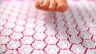 Women's foot on acupuncture massage mat. Close Up video