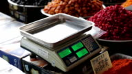 Women's hands are placed on the scales of dried fruit package video