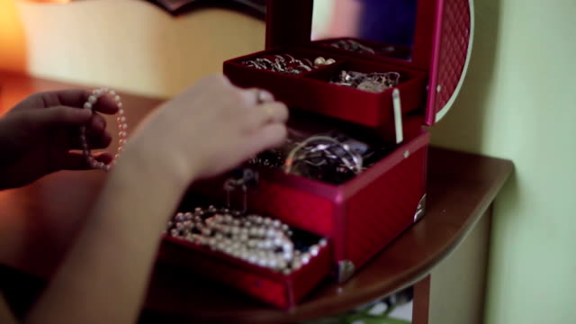 Women's hands being removed from the red box for jewelry bracelets. video
