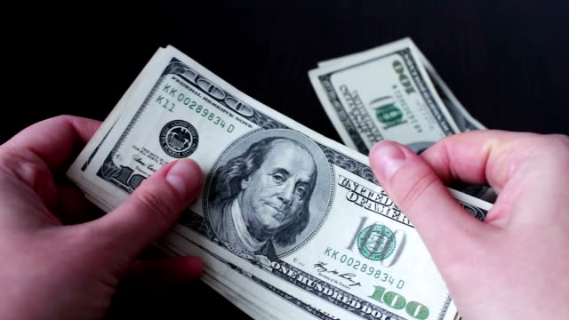 Women's hands holding a fan of hundred dollar bills and counts video