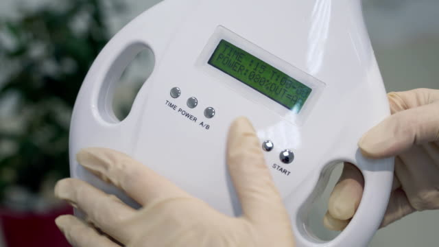 Women's hands in gloves starting a teeth whitening machine, Newest Laser Dental Bleaching. video