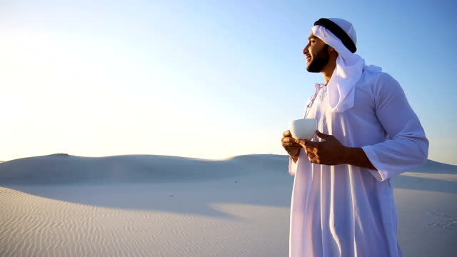 Wonderful beginning of morning for Arabian Sheikh guy in middle of huge desert over cup of coffee against blue sky in open air video