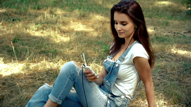 wonderful smiling girl sits on the grass on the street listening to music video