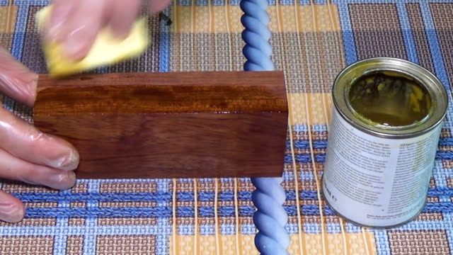 Wood beam palisander. The bar of solid wood is covered with stain. The girl covers a bar of rare wood with lacquer. The joinery impregnates the wood with wax. The end part of the wooden board video