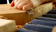 Wood carving - Human hand chiseling a piece of wood video